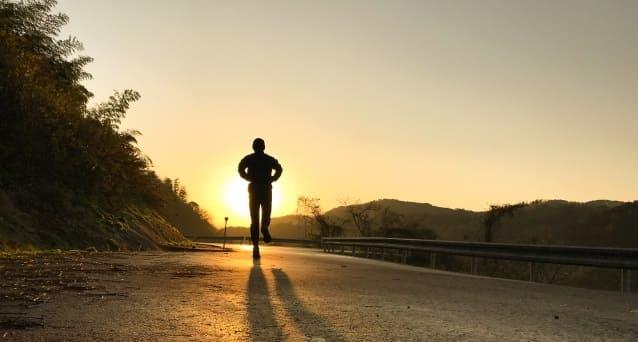 夕陽に向かってジョギングをする人