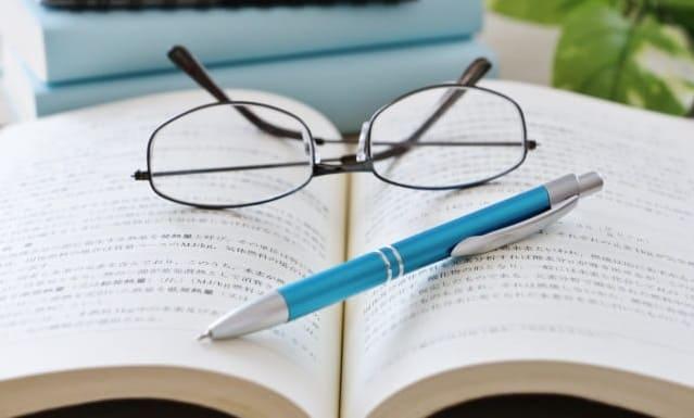 開いた本の上にシャーペンとメガネを置いている