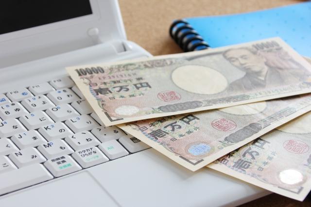 パソコンとお金の画像