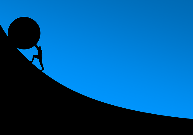 坂道で大きなボールを押し上げている画像