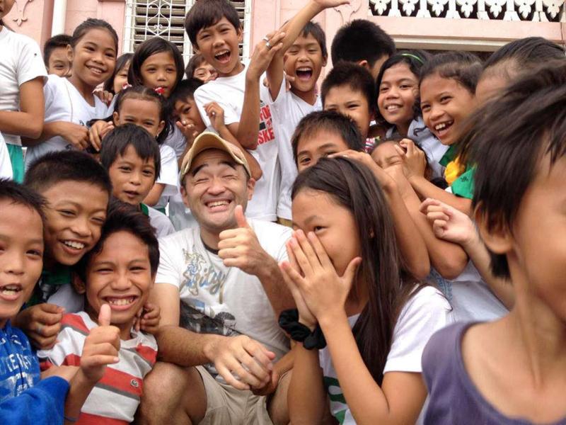 小学校の子供たちと笑顔で記念撮影をするカイトさん