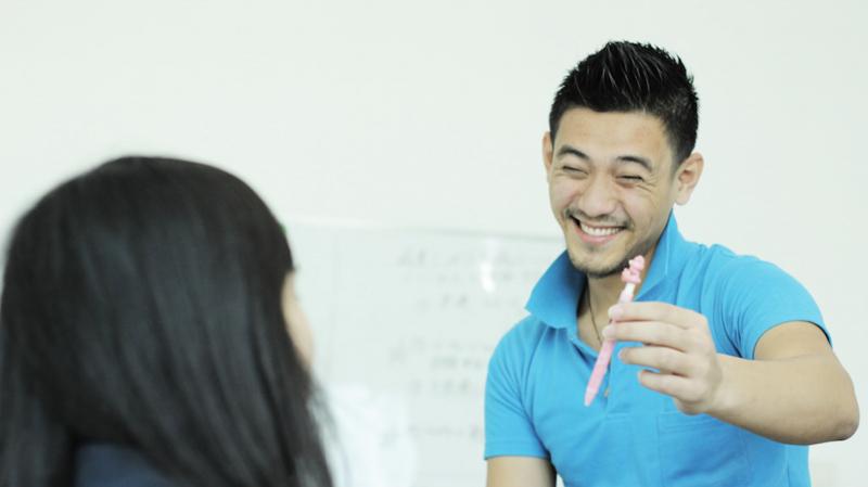 ペンを持った笑顔な英会話男性スタッフ