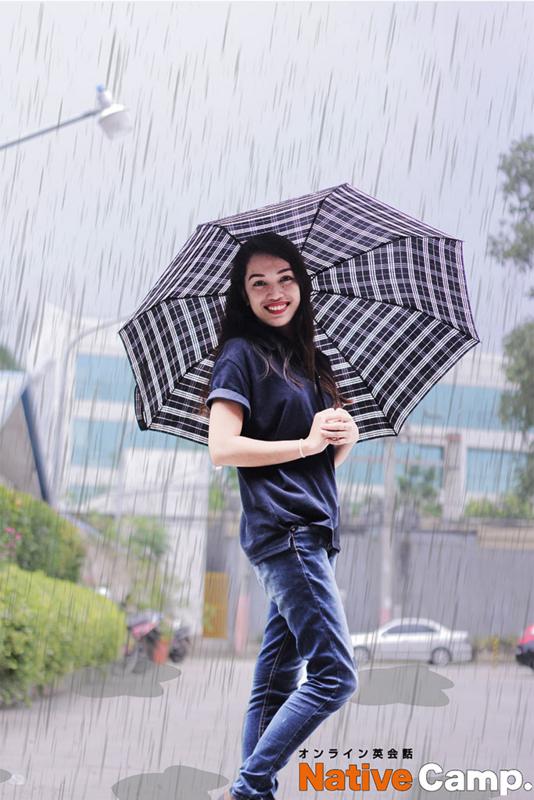 雨の中で傘をさし、ほほえむ女性(lauren)
