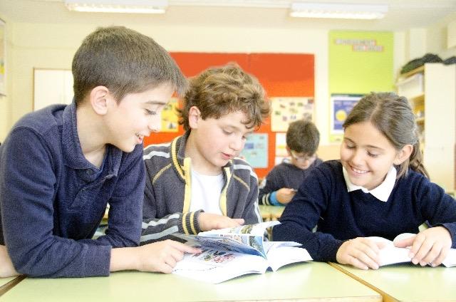3人の生徒が本を見ている