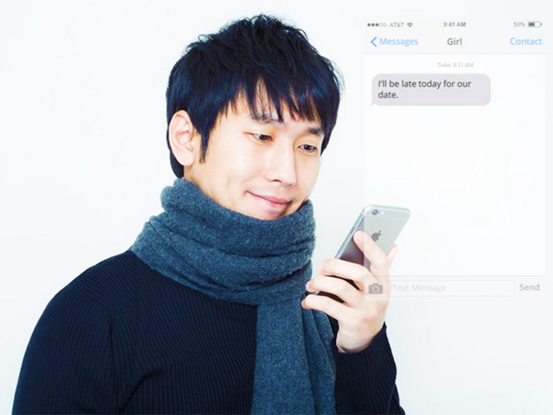 男性が携帯を持って微笑んでいる