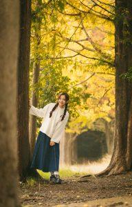 可愛い女性が木の横に立っている