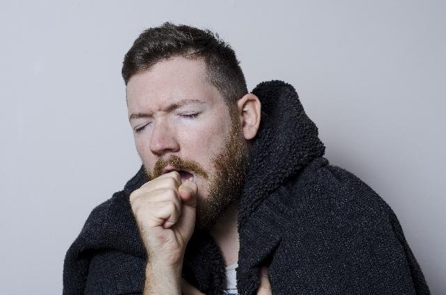 男性が咳き込んでいる写真