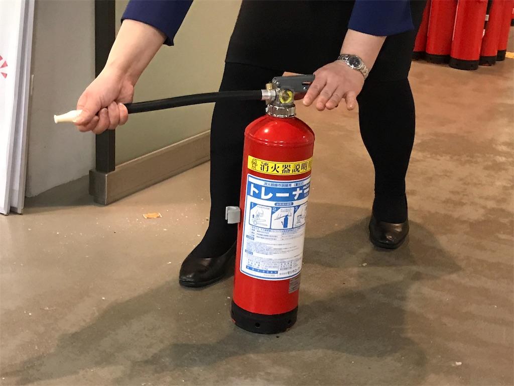 消火器の使い方を説明するガイドさん