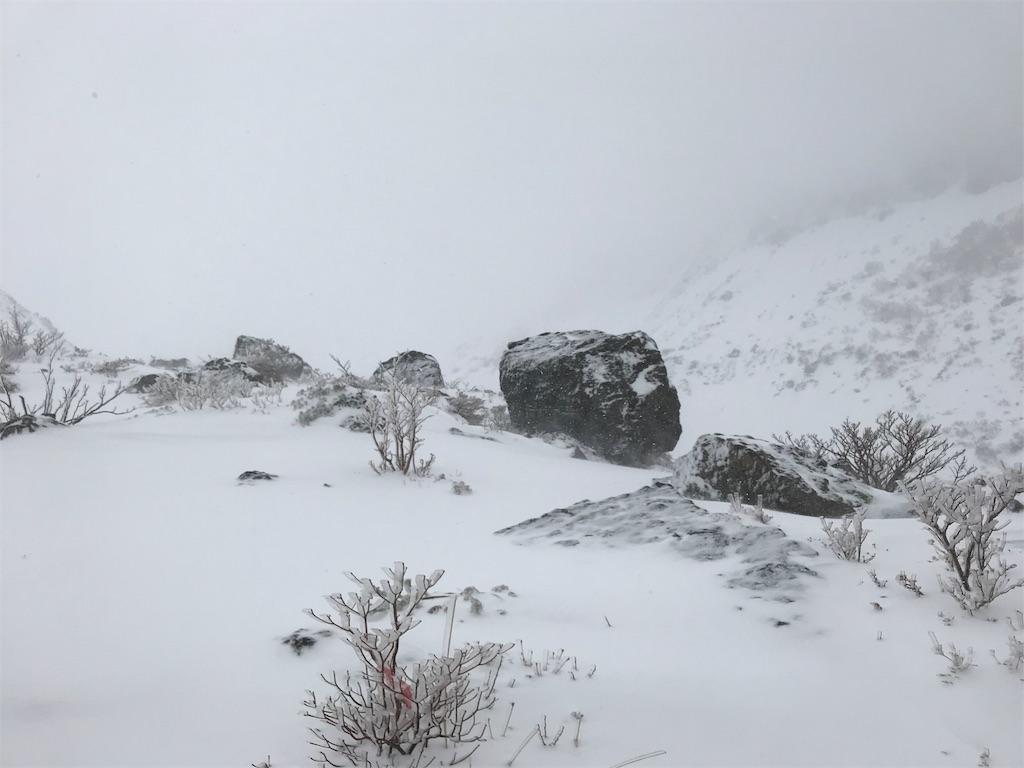 ホワイトアウトしていく中、かすかに見える大岩