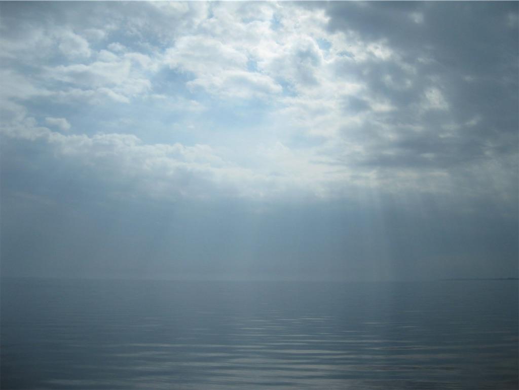 凪いだ湖面に光の柱がうつる