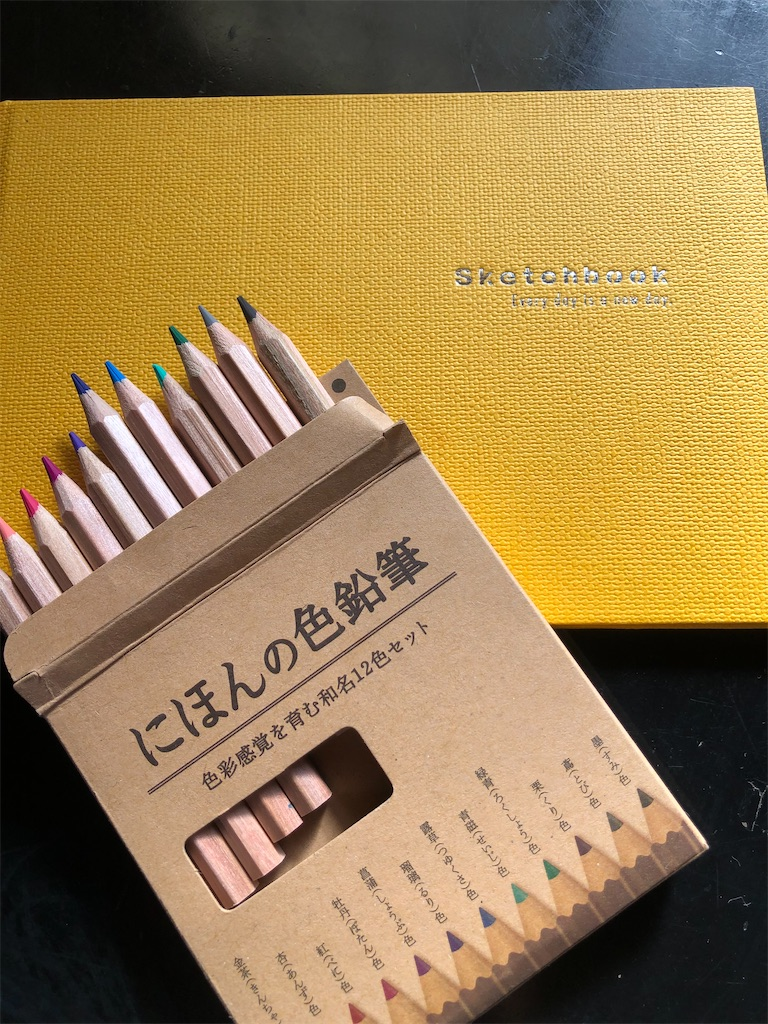 黄色いスケッチブックと12色の色鉛筆。