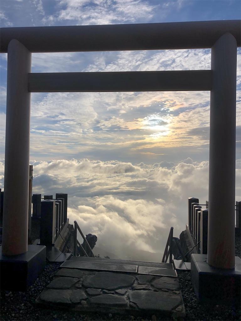 頂上鳥居の向こうに登る朝日。