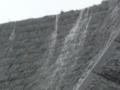 雨が滝と化している石垣