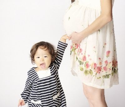 ママのお腹に手を触れる子供