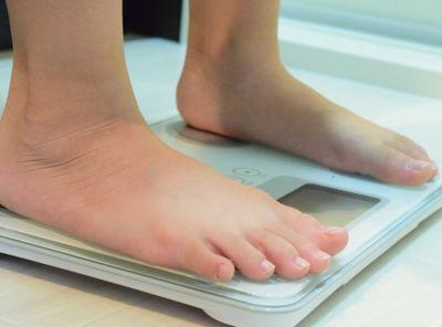 体重管理のために体重計に乗る