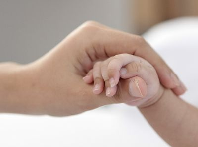 生まれた直後の赤ちゃんの手をもつわたし