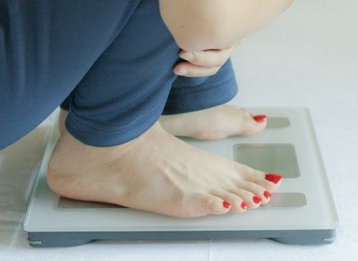 体重計に乗って体重を気にする女性