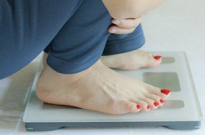 妊娠中の体重管理で体重計に乗る妊婦さん