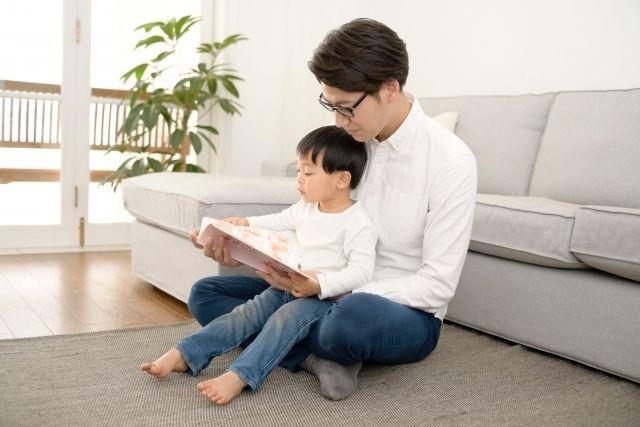 子どもに絵本を読んであげるパパ