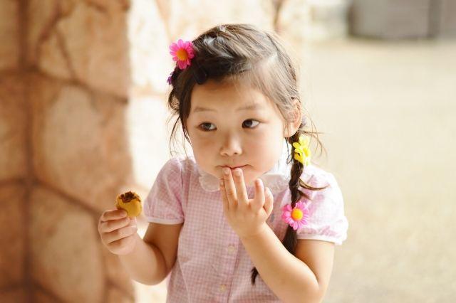 こっそりおやつを食べる女の子