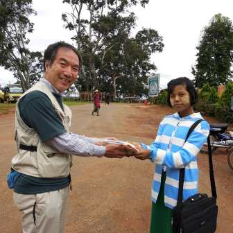 日本人のおじさんがミャンマーの女子高校生にプレゼントを渡している