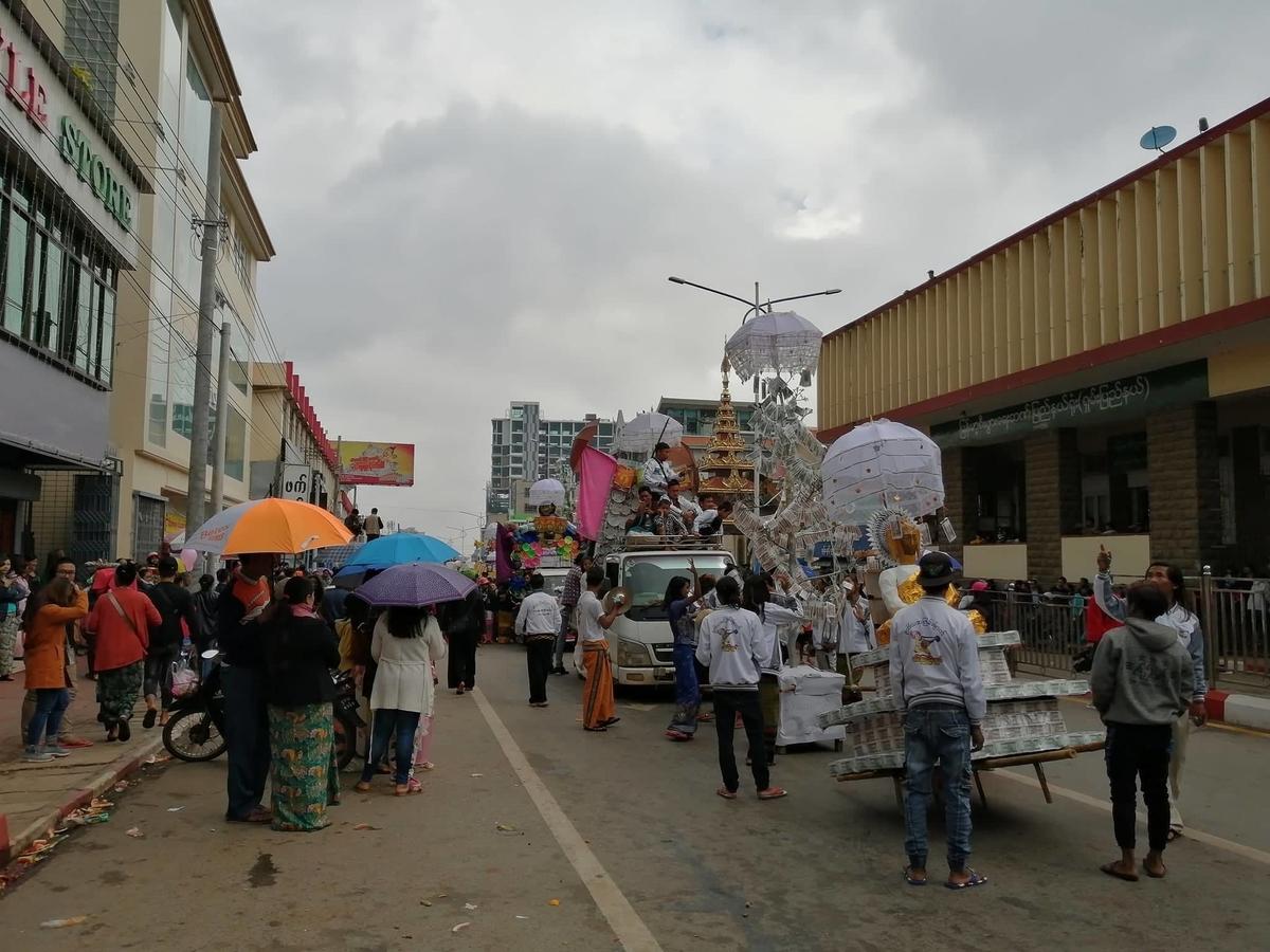 ミャンマーのカテイン祭りで道路をパレードしている写真