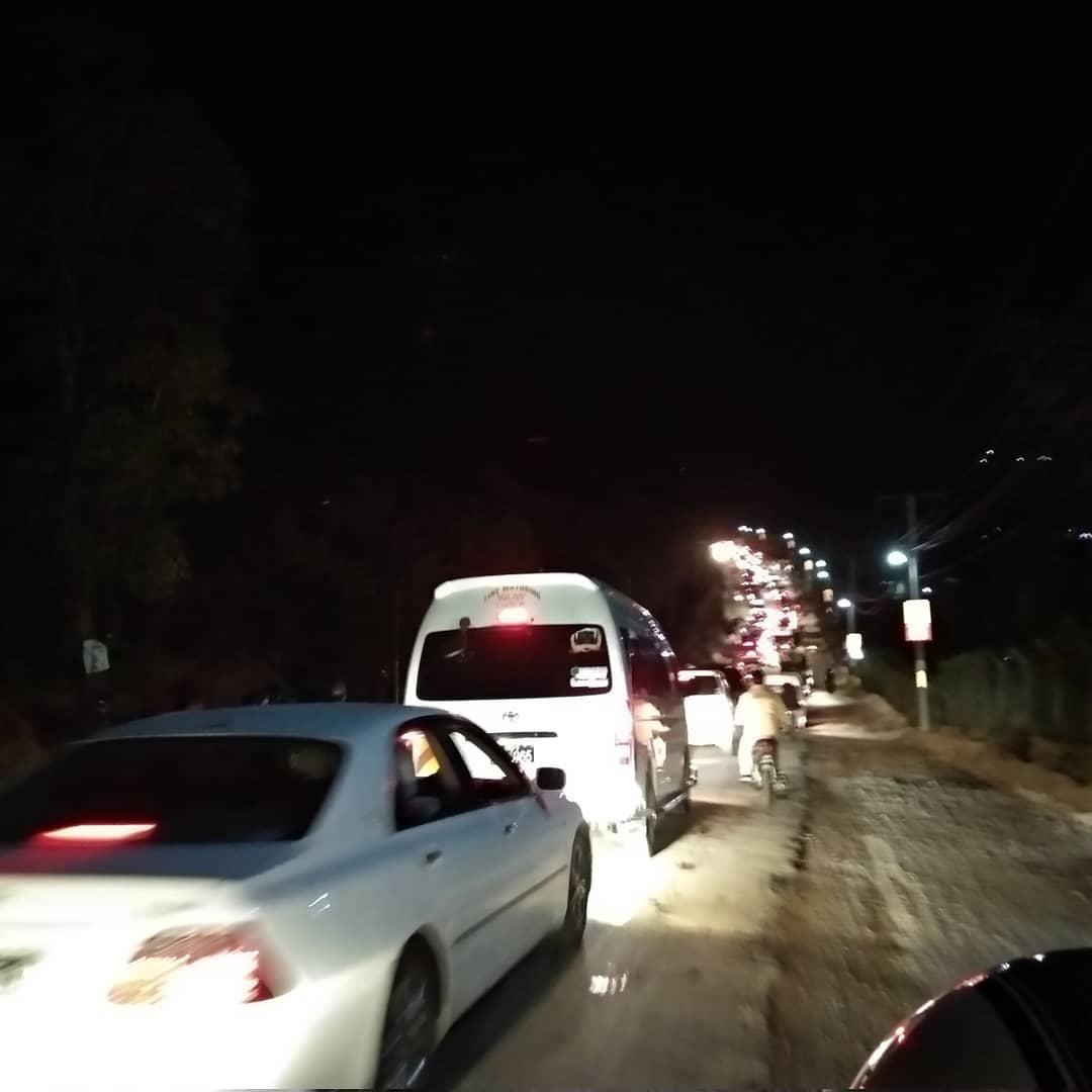 夜、車の渋滞の中、ランタンが空に舞う写真