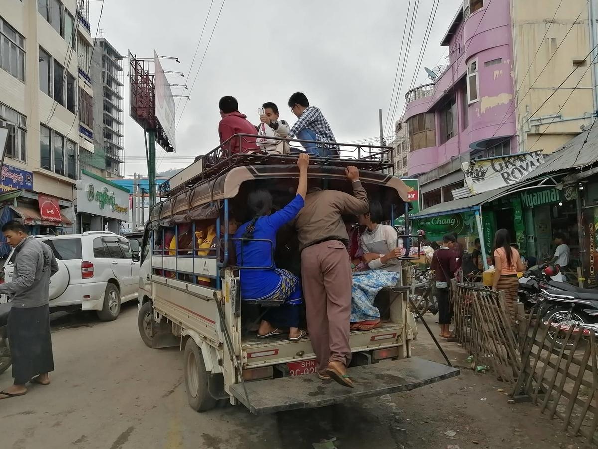 トラックの荷台に座席を付けた乗り合いバスの写真
