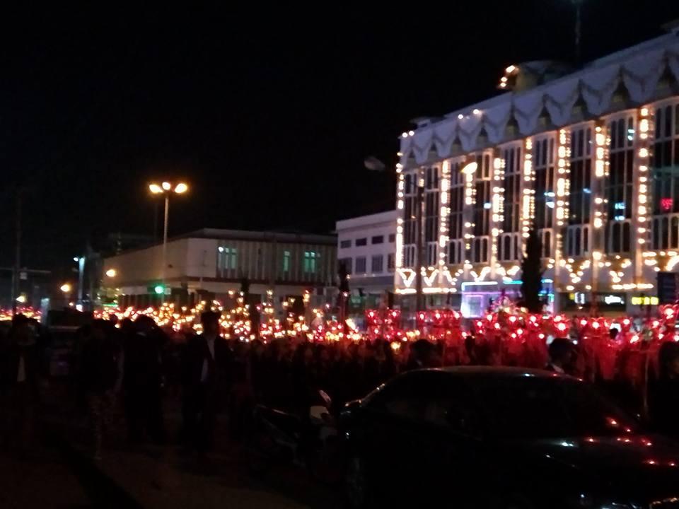灯篭を持った集団が道路を行進する写真