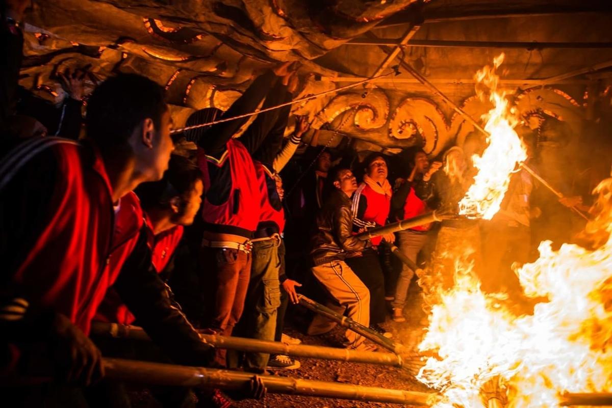 タイマツで気球に熱い空気を送り込む男達の写真