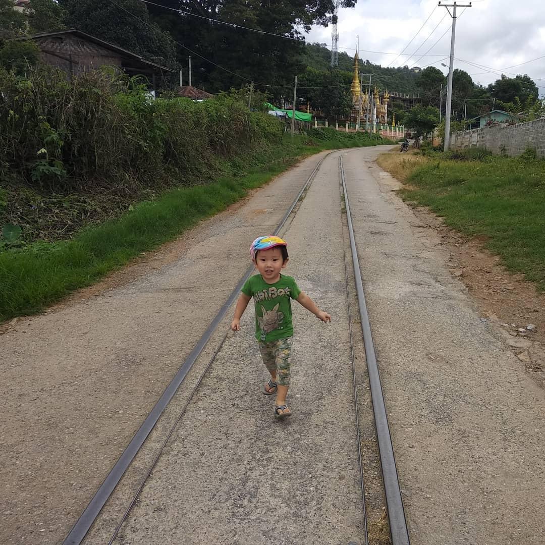 線路と道路が一緒になったところを歩く児童