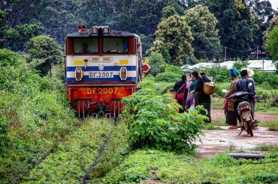 ミャンマーの列車と、列車を待つ民族衣装を着た地元の人たち