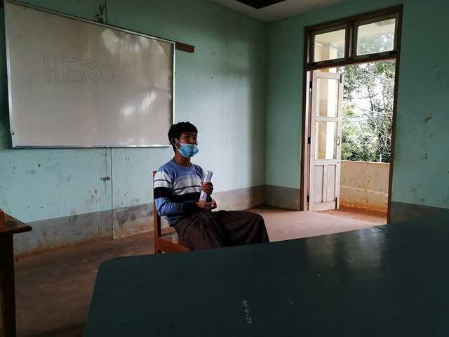 椅子に座って語る青年