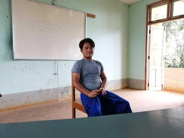 椅子の背もたれにもたれて座る青年