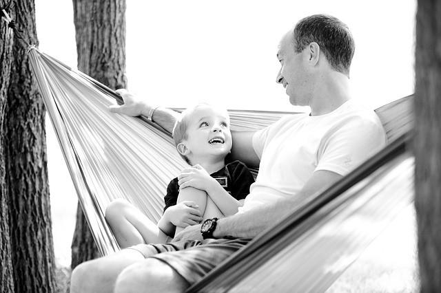 ハンモックで笑いながら子供と語り合う父親