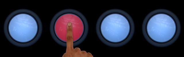 赤いボタンを人差し指で押そうとしている写真