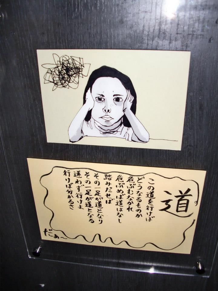 女の子が描かれたポストカードとアントニオ猪木の詩'道'を筆ペンで書いて無印の透明な壁掛けにおさめたもの