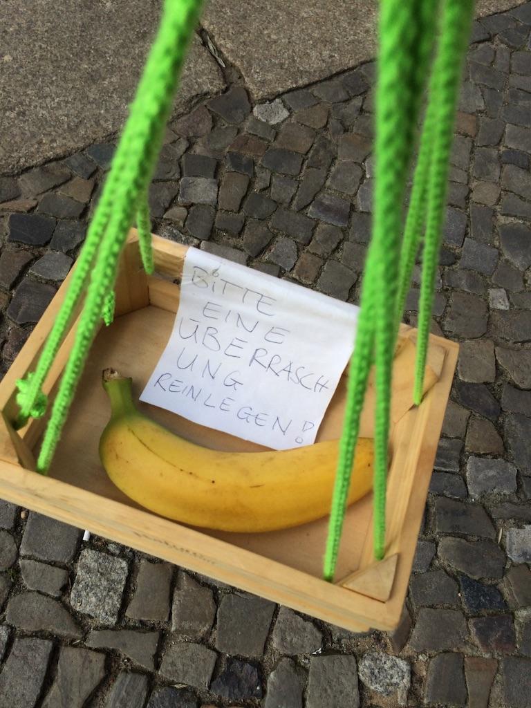 紐の先の箱の中にバナナが一つと、ドイツ語でサプライズを中に入れてください!と書かれた紙