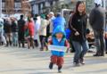 石巻市役所渡波支所で行われる配給の列に並ぶために走る男の子