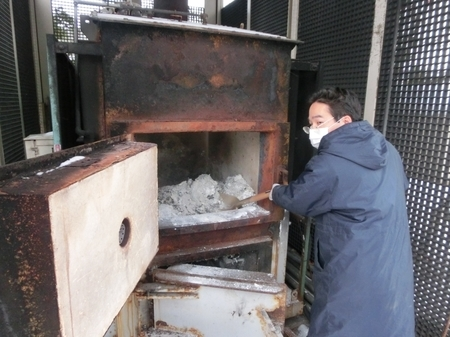 焼却炉での灰取り作業