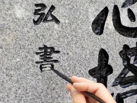 記念塔に刻まれている文字の補修作業