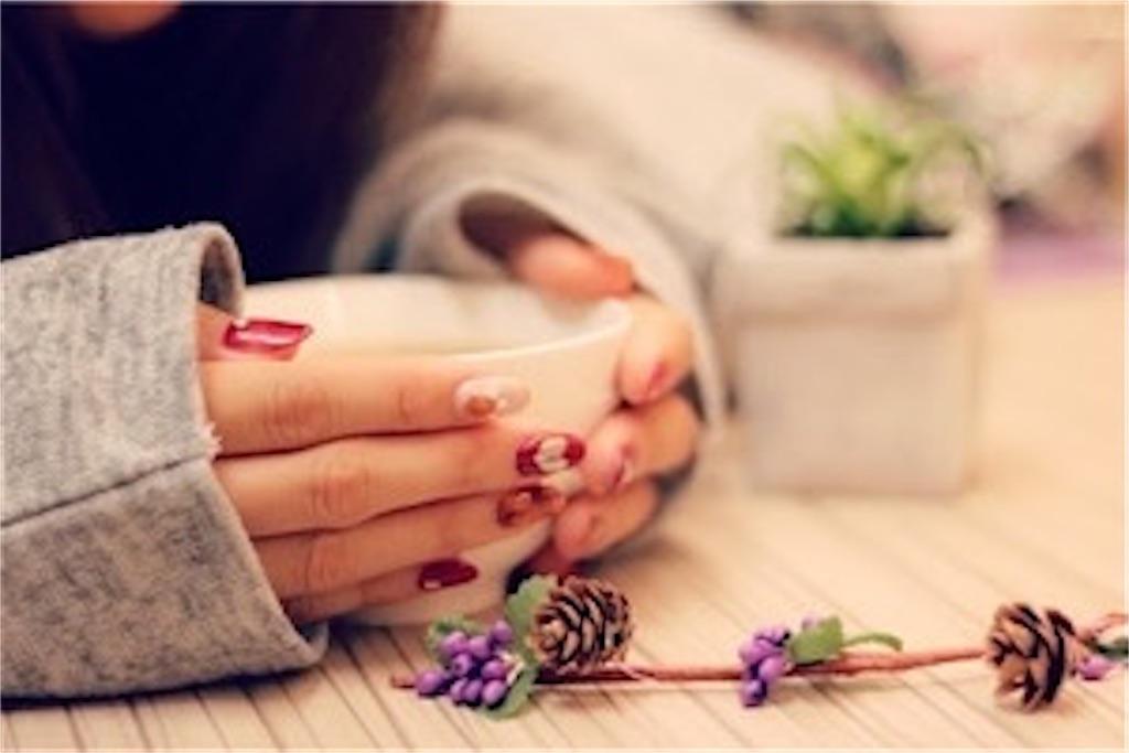 マグカップを温かそうに両手で包む女性