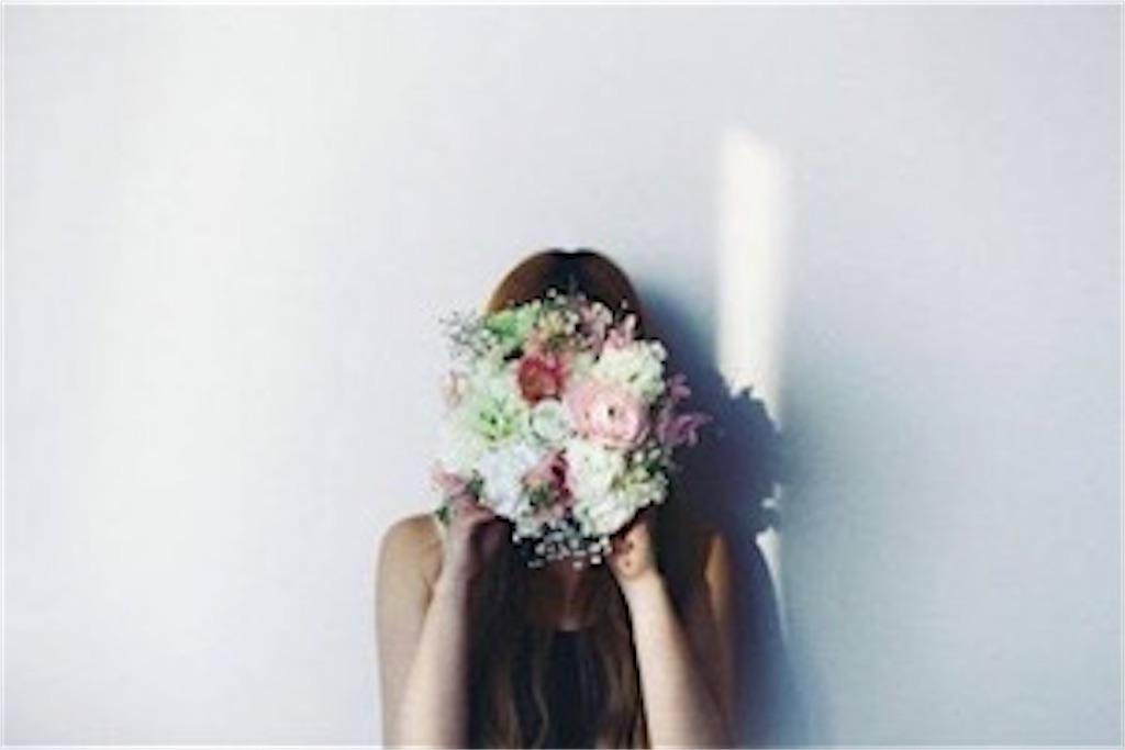 花束で顔を隠している女性