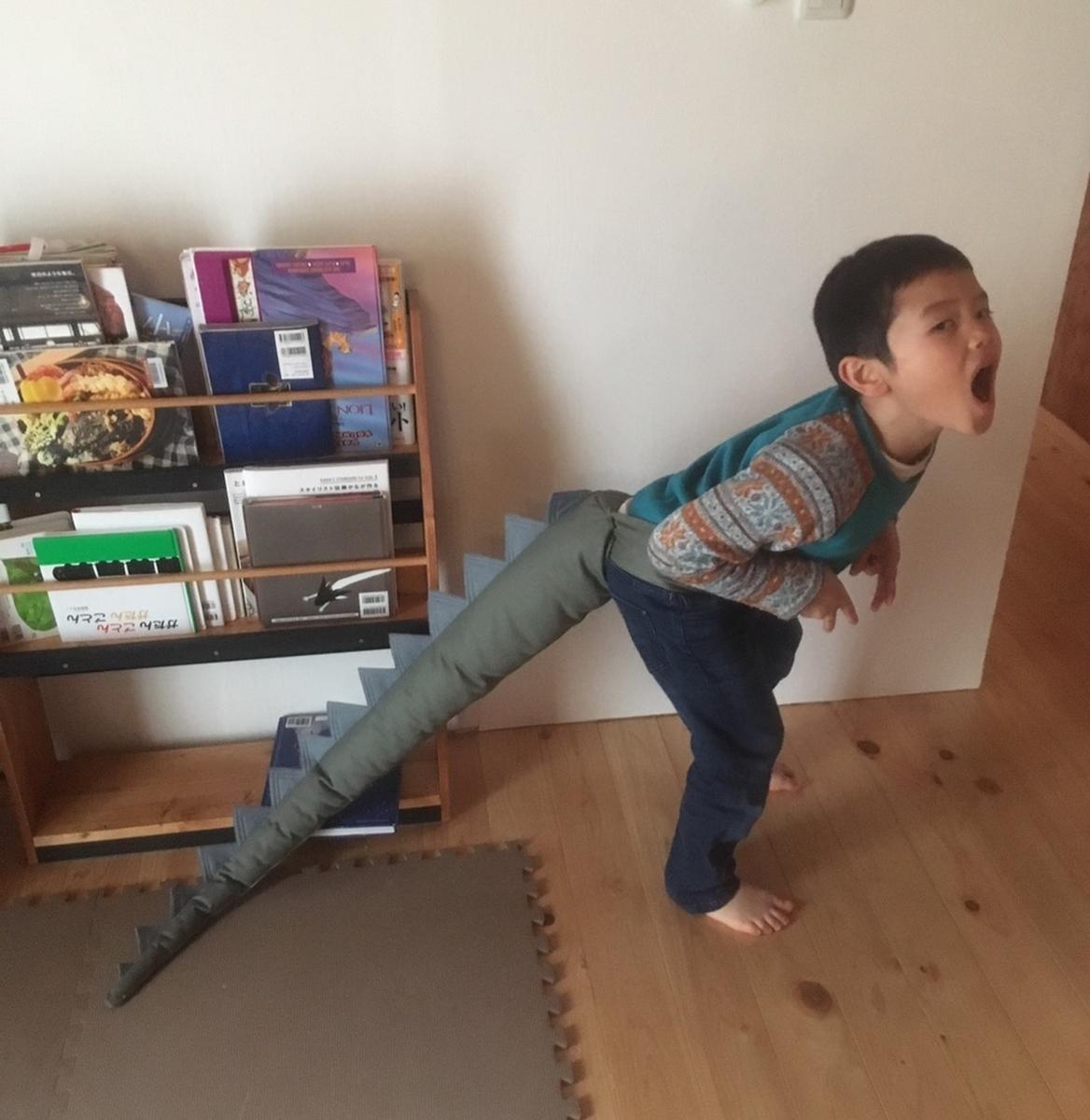 恐竜のしっぽを付けて恐竜になりきっている子供