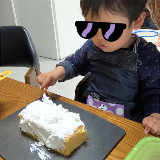 ケーキをデコレーションする2歳児