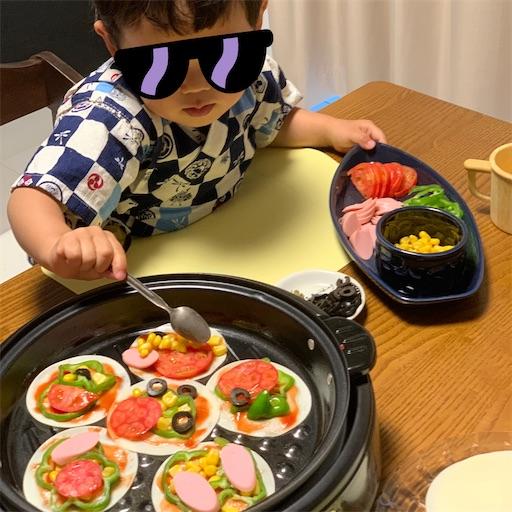 餃子の皮ピザに具材をのせる子ども