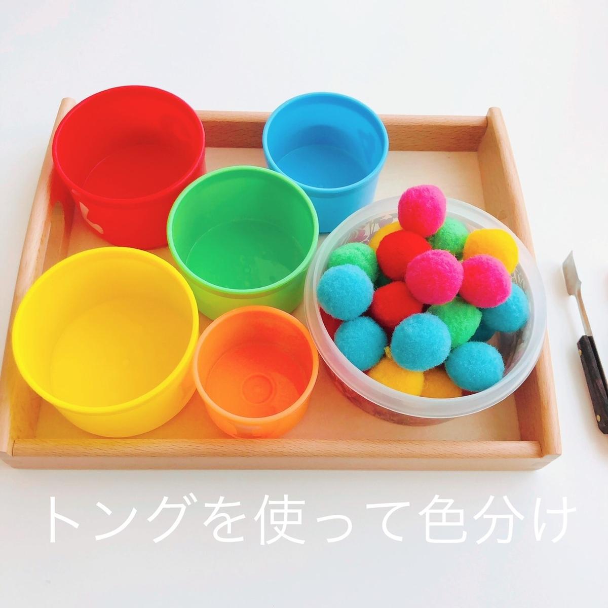 トングを使って色分けするおもちゃを上から撮影した写真