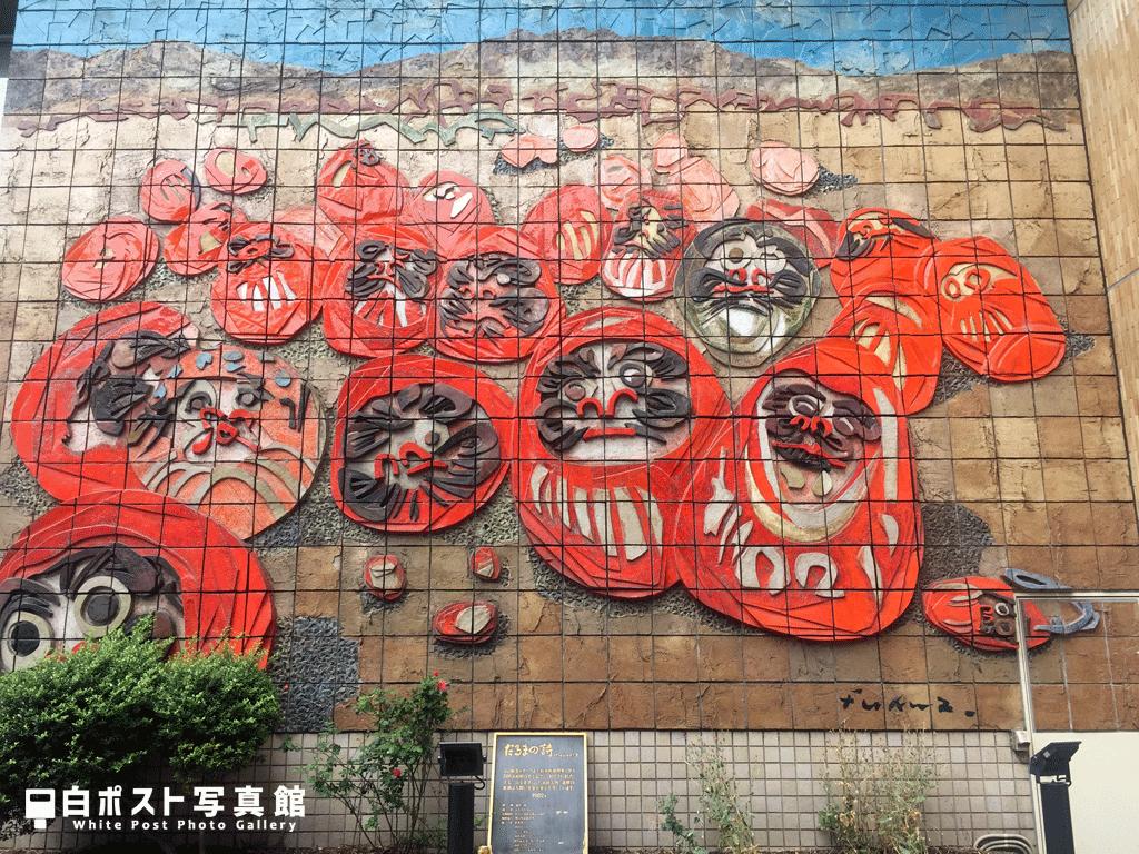 高崎駅前 陶板レリーフ「だるまの詩」