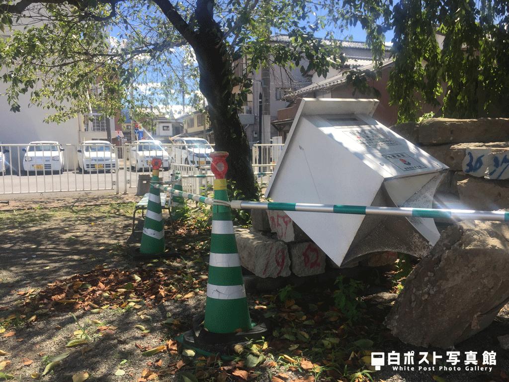 倒壊する三角公園の白ポスト