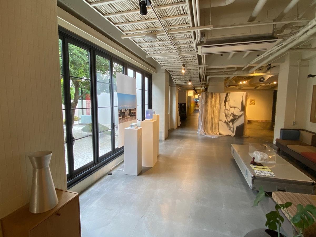 写真_窓から外が見え、通路にテーブルとソファーがあり、通路の窓側には美術作品が展示されている。